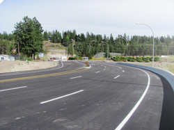 Completed Highway 97 overpass, fully paved with roadway lane markings, street lights and a cememnt saftey barrier.