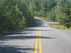 The New Cumberland Road project included repaving the road, replacing culverts, fixing hazardous road surface break-up with asphalt patches, and installing new shoulders