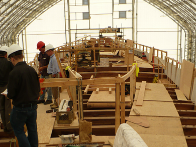 Workers examine plans and survey the top structure before beginning the interior and topside reconstruction.