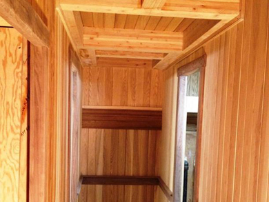 View of the wooden exposed beams and walls of the inside cabin hallway.
