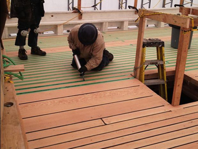 Workers sealing between each plank of the main deck.