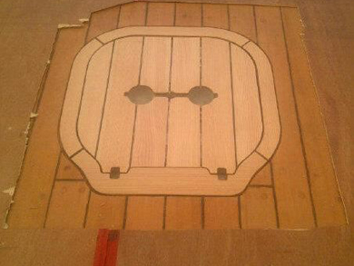 Wooden plywood sheets surround a cut out around the escape hatch,showing the detailed wood work.