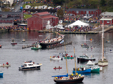 The Bluenose II floating in the harbour, surrounded by other sailboats; people line the shoreline and docks to watch.