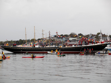 The Bluenose II floating in the harbour; people in kayaks and other boats look on.