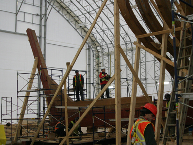 Shrouded in a temporary shelter, the shipwrights examine the wooden hull main beam (keel) and begin to reinstall the hulls ribs.