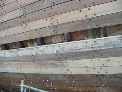 A mix of new and old hull planks being fastened to each rib by bolts.