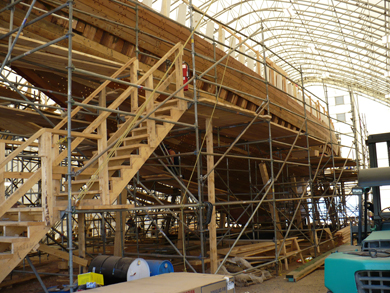 The entire hull with all the hull planks in place, save a few. Stairs to the topside are visible as is the scaffolding around the ship.