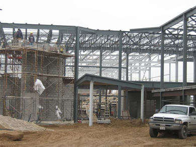 Workers construct a brick exterior wall along the newly installed metal girder frame, which will become the new Regional Recreation Complex