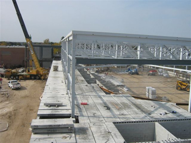The cement walls, metal roof girders and supports are installed using a crane and other construction vehicles