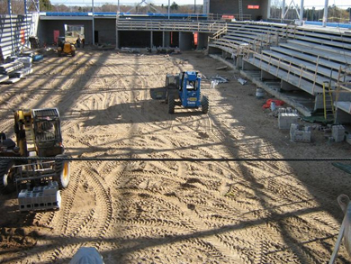 With the tiered, concrete bench seating area already in place, workers use forklifts to move cement blocks across the dirt floor, which will become the arena ice pad