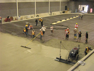 Construction workers lay concrete across the complex's interior floor