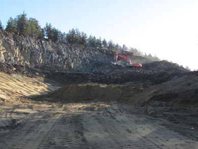 An excavator removes earth from the hillside to prepare for building the road bed.