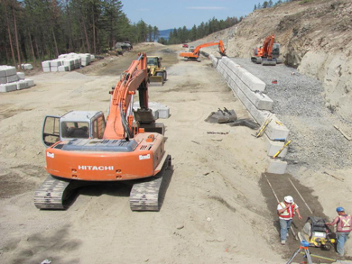 Three excavators and construction workers install a concrete block retaining wall.