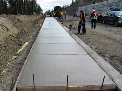 Construction crew pouring and smoothing out a new concrete sidewalk.