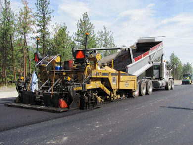 A dump truck and asphalt machine laying a second layer of asphalt on the roadbed.