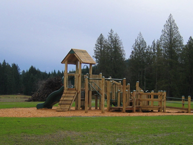 A new wooden play structure on sand, in a grassy area of the new community park
