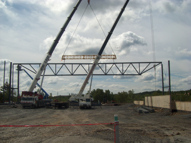 Photo: Two cranes install steel posts and beams one after the other.