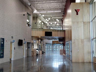 Photo: large open hallway with crossover pedestrian hall, shiny floors and marble wall of new Young Men's Christian Association.
