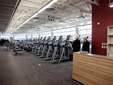 Photo: A large, carpeted room full of stepping, cycling and elliptical exercise equipment in front of a wall full of windows.