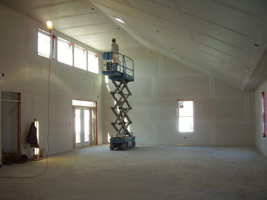 A construction worker uses an electric lift truck to install sheet rock and tape the interior walls and ceiling