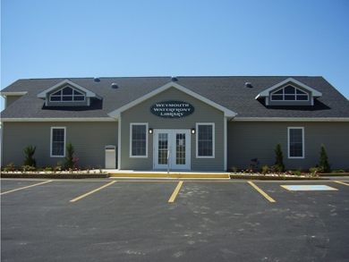 The front of the new Weymouth Public Library building, with grey siding exterior walls and a paved parking lot