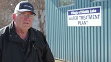 Man beside building with sign that says 'Village of Middle Lake WATER TREATMENT PLANT'