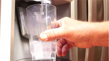 Hand holding glass with clean drinking water