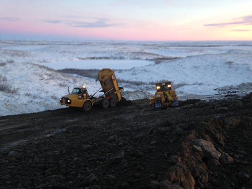 Dump truck pouring materials at construction site on the Inuvik to Tuktoyatuk Highway