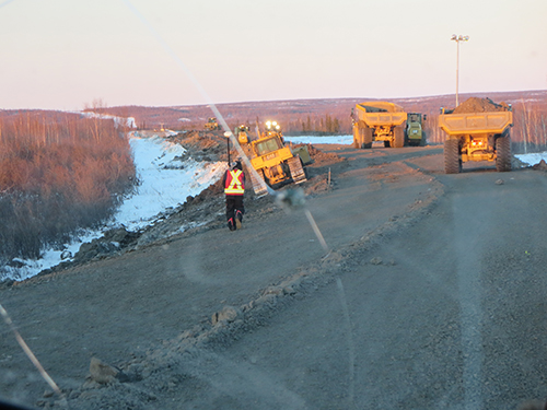 Construction vehicles on berm being built for the Inuvik to Tuktoyatuk Highway