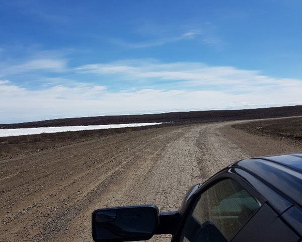 A car on the Inuvik to Tuktoyaktuk highway in the spring of 2018 after it was just opened. The highway is a gravel surface surrounded by local plants and a river.